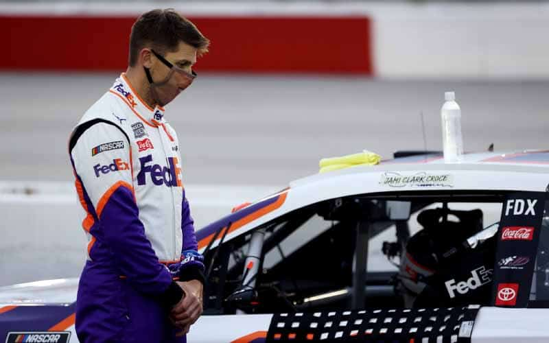 NASCAR driver standing next to car with COVID-19 face mask on