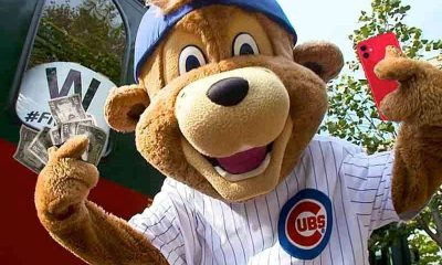The Chicago Cubs mascot holding an iPhone and some cash