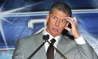 Vince McMahon looking confused with his hand placed on his head