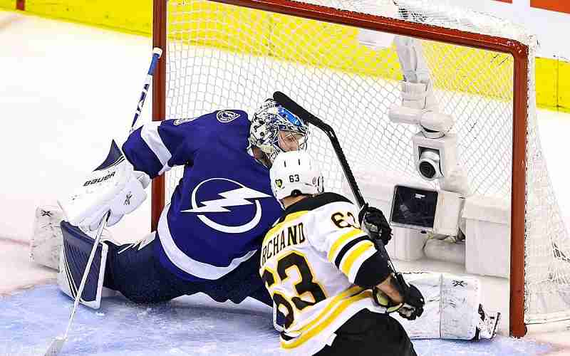 Bruins player shooting the puck against the Lightning goal keeper