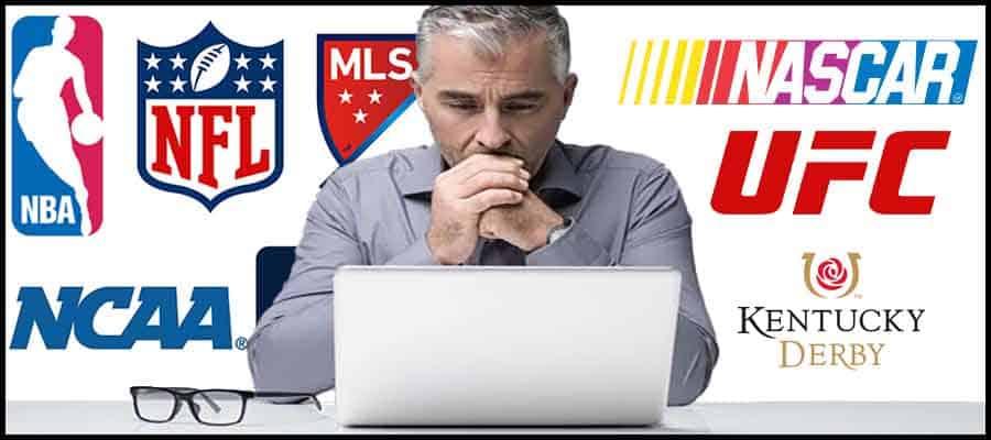 Man sitting at computer with sports logos