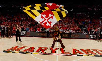 Maryland Terrapins mascot waving a flag on their basketball court