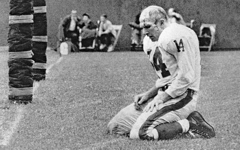 sad quarterback ya tittle kneeling in defeat