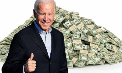 Biden giving a thumbs up in front of a pile of cash