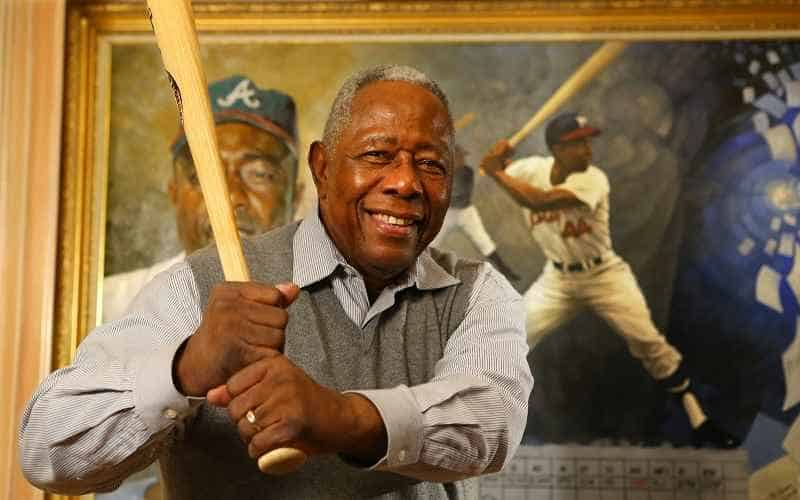 mlb home run king hank aaron posing with a bat in front of his portrait