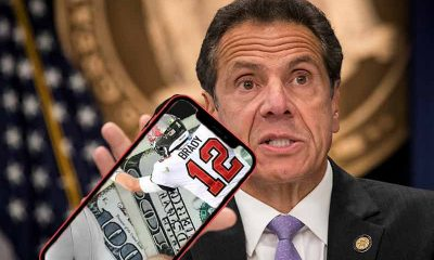 Governor Cuomo holding a smartphone with a mobile sportsbook app pulled up